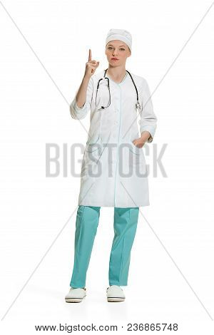 Beautiful Young Serious Woman In White Coat Pointing Up By Finger At Studio. Full Length Shot Isolat