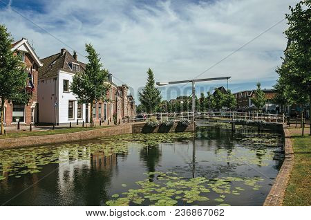 Tree-lined Canal With Aquatic Plants, Streets On The Banks, Brick Houses And Bascule Bridge On A Sun