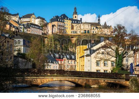 a view of the Alzette River as it passes through the Grund Quarter in Luxembourg City, Luxembourg, and the Ville Haute Quarter on the top left, highlighting the belfry of the Saint-Michel church
