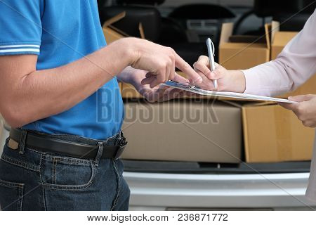 Woman Signing Signature On Clipboard To Receive Package From Delivery Man. Male Postal Courier Perso