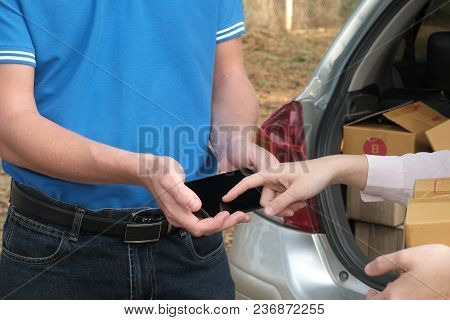 Woman Signing Signature On Smart Phone To Receive Package From Delivery Man. Male Postal Courier Per