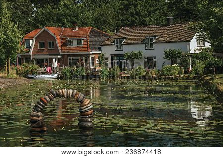 Tree-lined Canal With Aquatic Plants, Boats On The Banks And Brick Houses On A Sunny Day In Weesp. Q