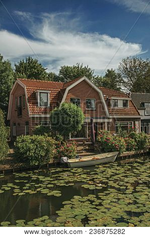 Tree-lined Canal With Aquatic Plants, Boats On The Bank And Brick House On A Sunny Day In Weesp. Qui