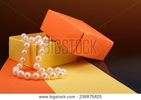 Pearl Beads In Opened Homemade Yellow And Orange Paper Gift Box On Dark Background. Toned Light