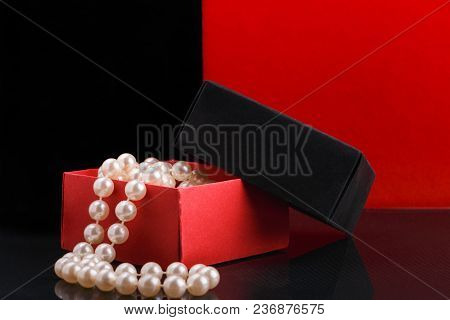 Pearl Beads In Opened Homemade Black And Red Paper Gift Box On Glossy Surface