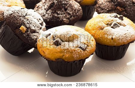 A Selection Of Muffins With Powder Frosting On White Reflective Work Surface, Shot At Angle