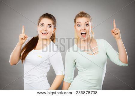 Gestures, Having Idea Concept. Happy Two Women Pointing Up With Finger. Studio Shot On Light Dark Ba