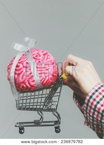 Woman Hand Holding Shopping Cart With Brain Inside. Clever, Responsible Buying Concept.