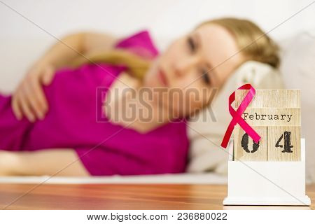 Woman Lying On Bed Looking At Calendar, It Is 4 February World Breast Cancer Day, Date With Pink Awa