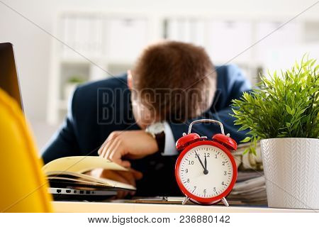 Red Alarm Clock Shows Late Time Closeup And Tired Office Male Clerk In Suit Take Nap On Table Workpl