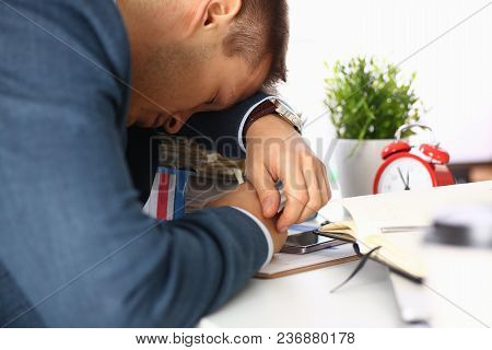 Tired Office Male Clerk In Suit Take Nap On Table Workplace Full Of Exam Papers. Sleepy White Collar