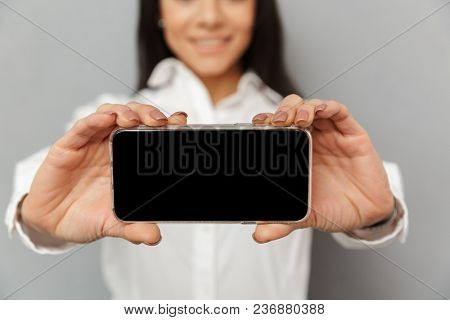 Photo cropped of brunette woman 30s in office wear holding cell phone in hands and demonstrating copyspace black screen on camera isolated over gray background