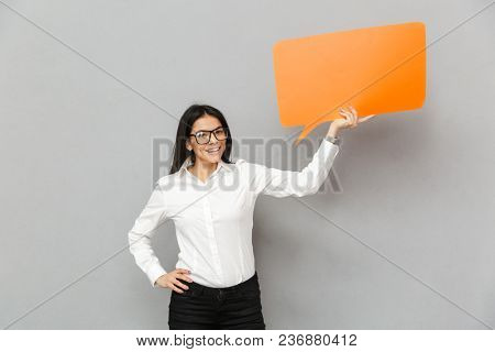Photo of smiling office woman wearing businesslike outfit holding empty copyspace bubble for your text and looking on camera isolated over gray background