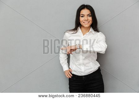 Portrait of beautiful woman with long brown hair wearing white shirt smiling at camera and pointing finger aside on copy space isolated over gray background