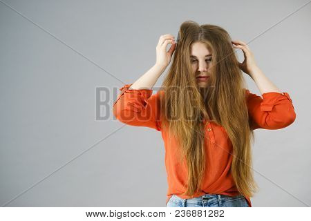 Funny Teenage Woman Having Problem With Tangled Tousled Hair. Haircare Problems Concept.