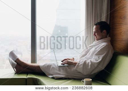 Young Smiling Businessman Working On Laptop Computer Wearing White Bath Robe Sitting Near Window Wit