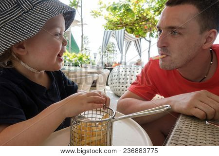 Playful Man With Fries In Mouth Having Fun And Making Charming Boy Laughing Sitting In Restaurant Of