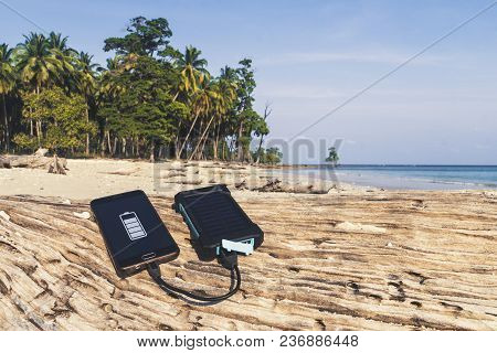 Battery Solar Energy Device On A Background Of The Sandy Beach Of An Uninhabited Island. Charge Smar