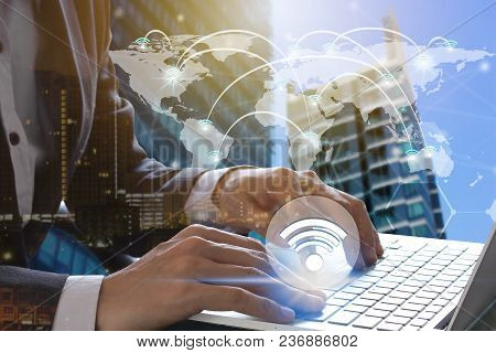 Businessman Hand Use Laptop With Wifi Icons Connection And Network Communication On Map World.