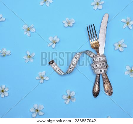 Iron Fork And Knife Wrapped In A Measuring Tape On A Blue Background, Top View