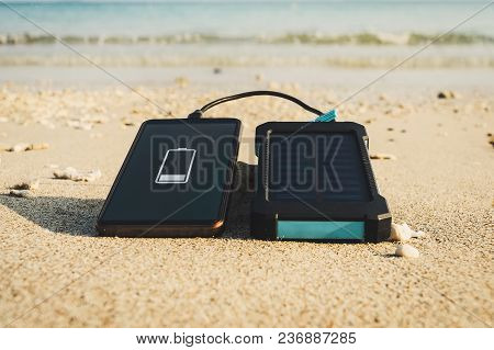 Portable Solar Panel Is On The Beach In The Sand And Charges The Battery Of The Mobile Phone. Use Of
