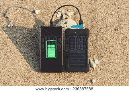 Portable Solar Panel Is On The Beach In The Sand And Charges The Battery Of The Frameless Mobile Pho