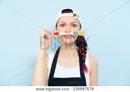 Young Beautiful Girl Brunette Painter, Designer And Worker Paints A Paint Roller And Brush Wall. The