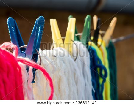 Woolen Colorful Threads Are Hanging On A Clothesline With Clothespins Outdoors