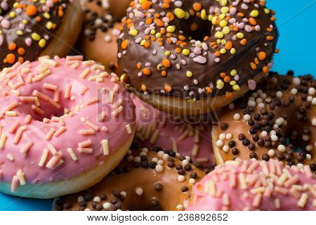 Assorted Donuts With Chocolate Frosted, Pink Glazed And Sprinkles Donuts. Close-up