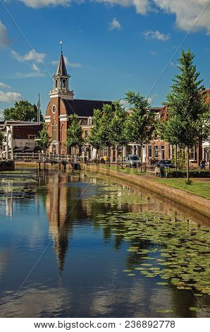 Tree-lined Canal With Bascule Bridge, Church, Brick Houses In Street On The Banks And Sunny Day At W