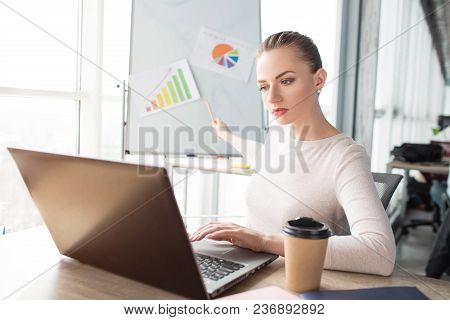 Girl Is Looking To The Laptop And Demonstrating Diagrams On The Desk. She Is Working Right Now. Youn