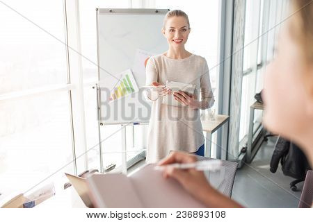 Cheerful And Happy Speaker Is Standin Near Flipchart With Diagrams. She Is Waiting While The Girl Wi