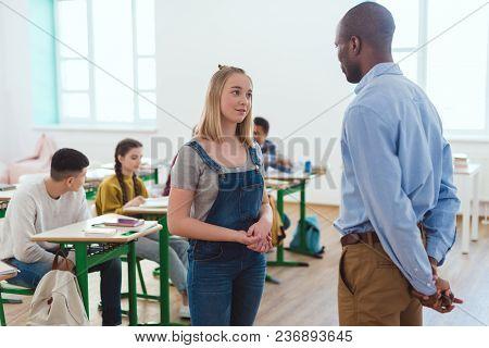 African American Teacher Talking To Teenage Schoolgirl And Classmates Sitting Behind