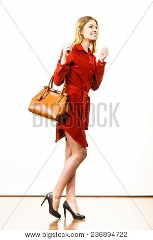 Fashionable Pretty Young Woman Wearing Elegant Casual Red Short Dress And Holding Leather Bag Presen