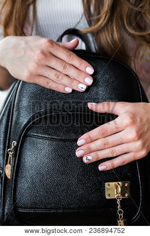 Fashionable stylish young woman handbag and pink manicure