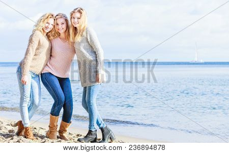 Three Fashionable Women Wearing Sweaters During Warm Autumnal Weather Spending Their Free Time On Su