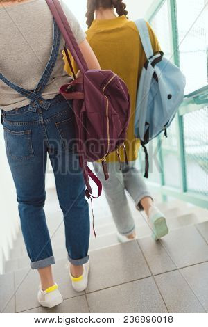 Cropped Shot Of Schoolgirls With Backpacks Walking Down Stairs At School Corridor