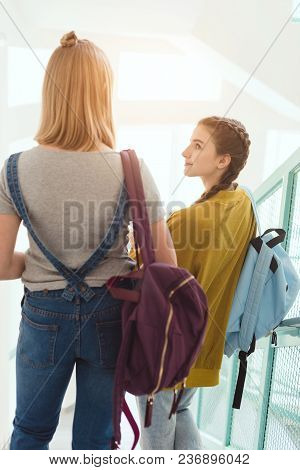 Rear View Of Schoolgirls With Backpacks Walking Down Stairs At School Corridor