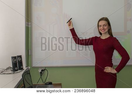 Portrait Of A Happy Teacher In The Classroom. Teacher Shows On An Electronic Board