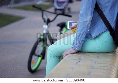 Young Teenage Girls With A Phone Sitting Next To A Bicycle. The