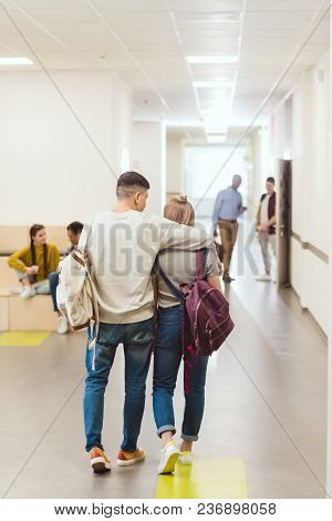 Rear View Of Teenage Students Couple Walking By School Corridor And Embracing