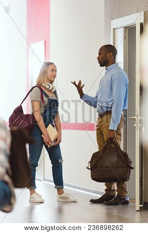 Teen Schoolgirl Talking With Teacher At School Corridor