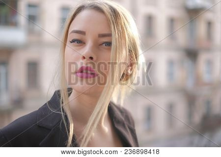 Portrait Of A Young Woman In A Black Suit Close-up Against A Background Of A Blurry City In The Rays