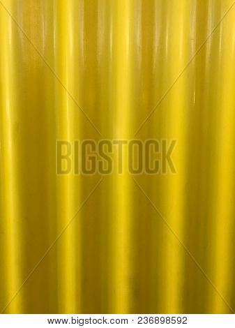 Sheet Of Yellow Painted Corrugated Iron In The Sunshine Creates Abstract Background