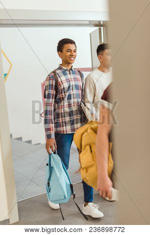 High School Students Walking By School Corridor On Break