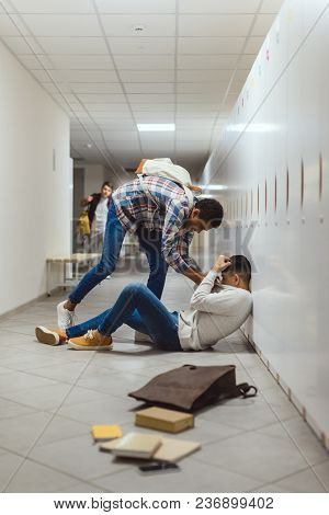 Schoolboy Being Bullied By Classmate In School Corridor Under Lockers While Other Boy Running To Hel