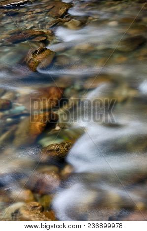 Long Exposure Of River Flowing Over Rocks.