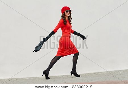 Glamorous Young Trendy Woman In Red Dress Walking