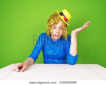Portrait Of A Young Woman In A Comic Pop Art Style Sitting At A Table. Shocked Female In Yellow And