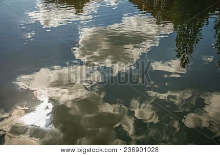 Clouds And Tree Reflected In Canal Water Surface On A Sunny Day In Weesp. Quiet And Pleasant Village
